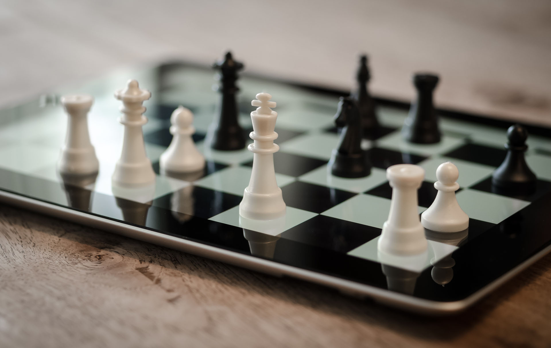 Photo of black and white chess pieces on a chess board.
